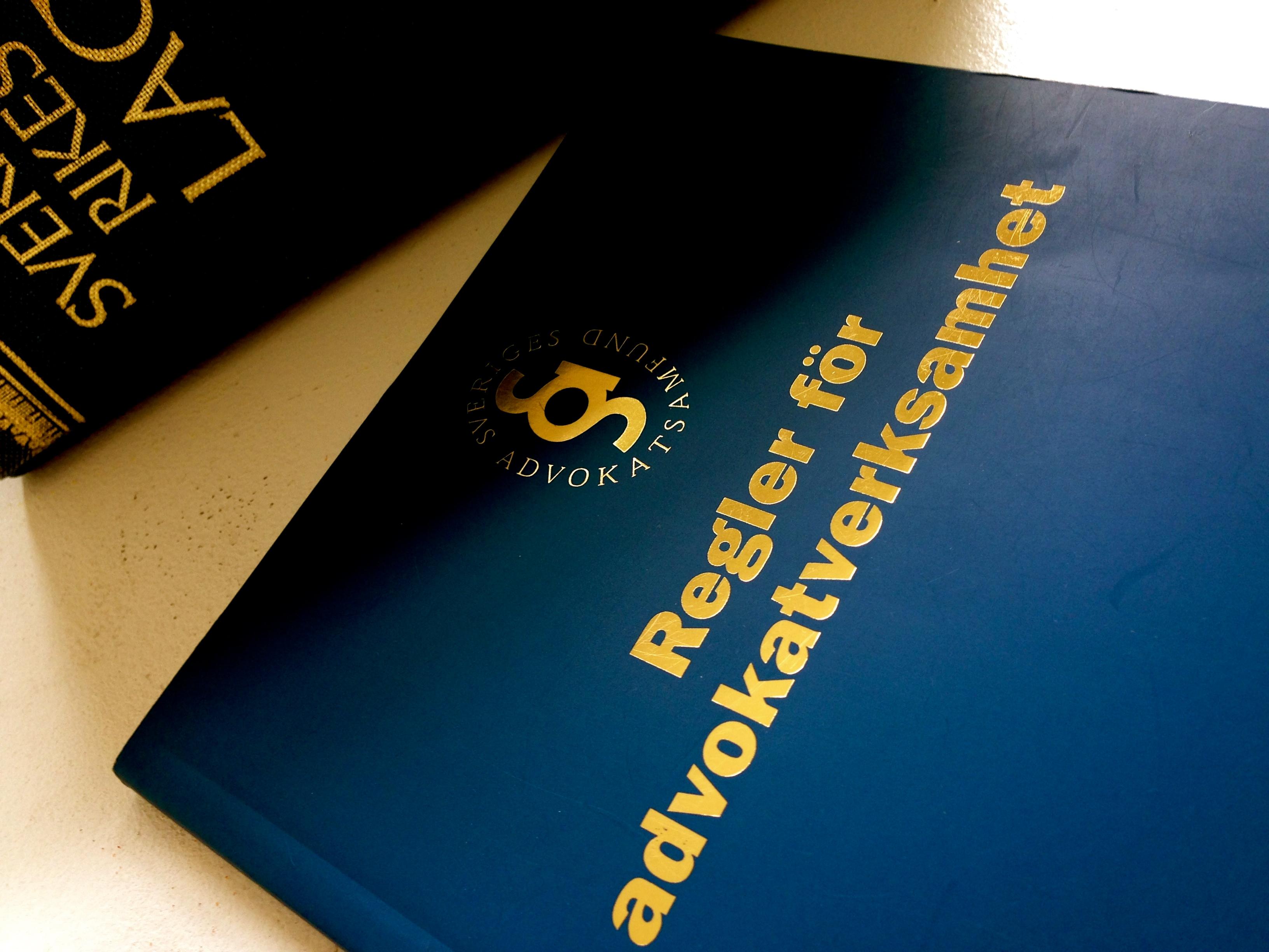 Två mörkblåa böcker ligger bredvid varandra. Fokus är främst på boken Regler För Advokatverksamhet och boken Sverige Rikets Lag visas i bakgrunden.